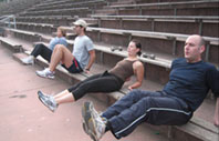 Boot camp abdominal crunches - doing reverse crunches in outdoor fitness bootcamp at Kezar Stadium in San Francisco